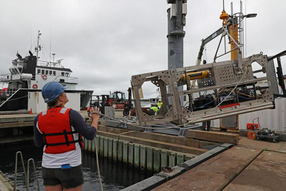 Kaitlyn Tradd, a mechanical engineer at Woods Hole Oceanographic Institution, helped a crane lift DEEP-SEE for testing.